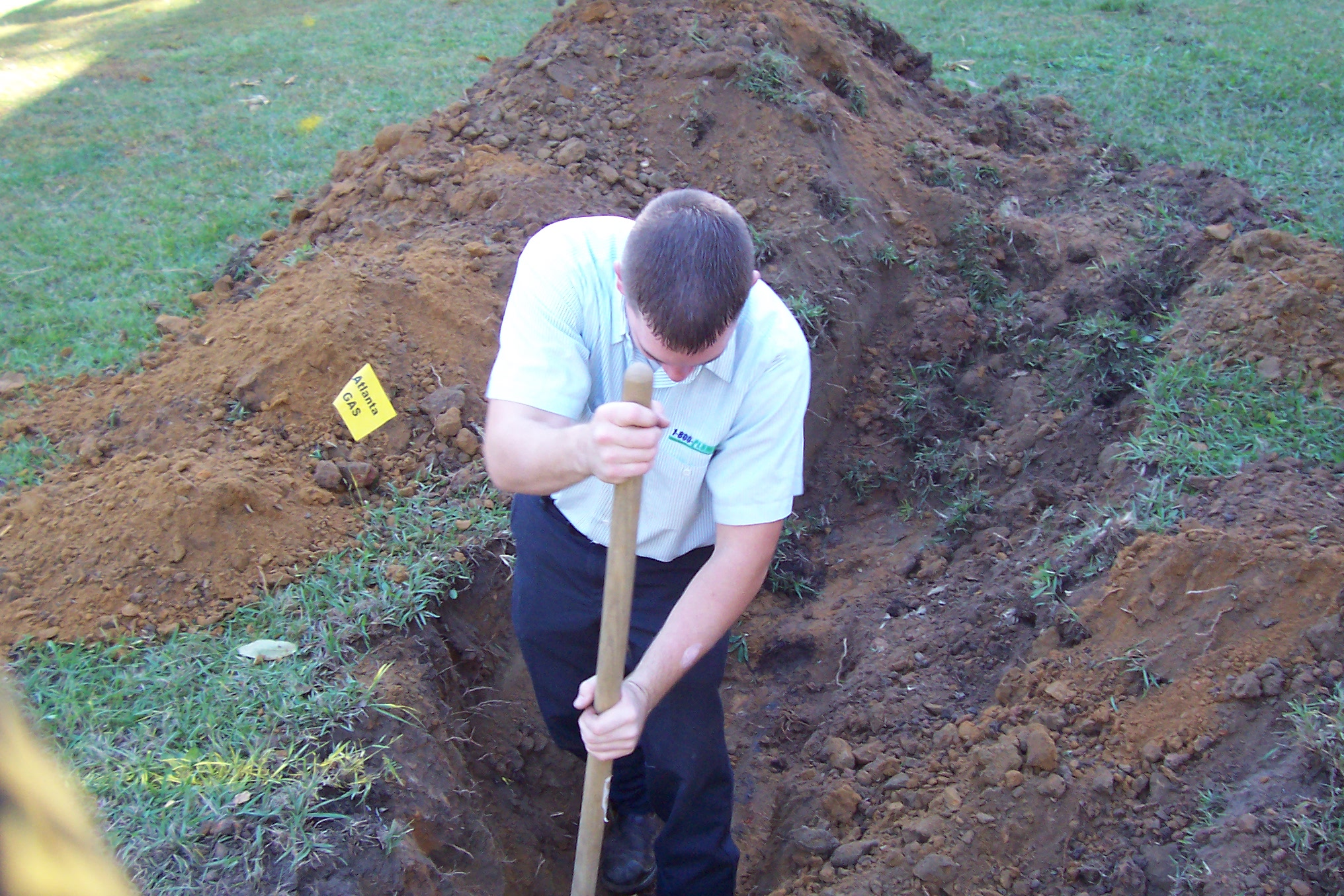technician digging a sewer line
