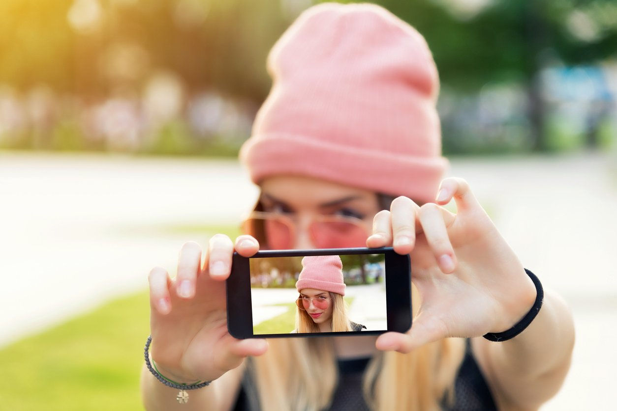 Young blonde in pink beanie taking a selfie for her Instagram Stories