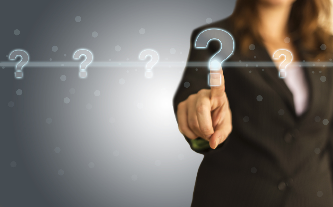 woman in business suit pointing at floating question mark