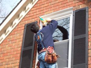 repairman putting sealant around a home window
