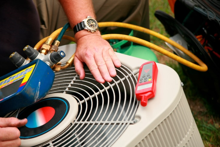 Technician inspecting air conditioner