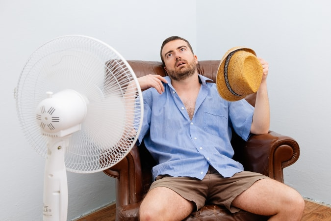 Man sweating because he doesn't have an air conditioner