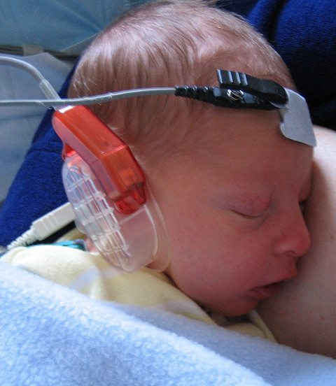 Infant undergoing a newborn hearing test while sleeping.
