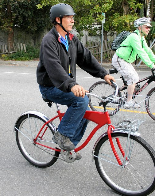 An elderly gentleman rides a bicycle wearing a helmet.