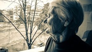 An eldery woman looking out the window
