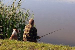 Older man fishing with his dog