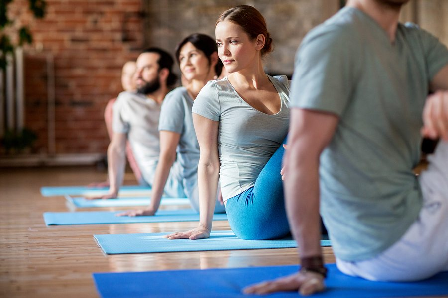 fitness sport and healthy lifestyle concept - group of people doing yoga seated spinal twist pose in gym or studio