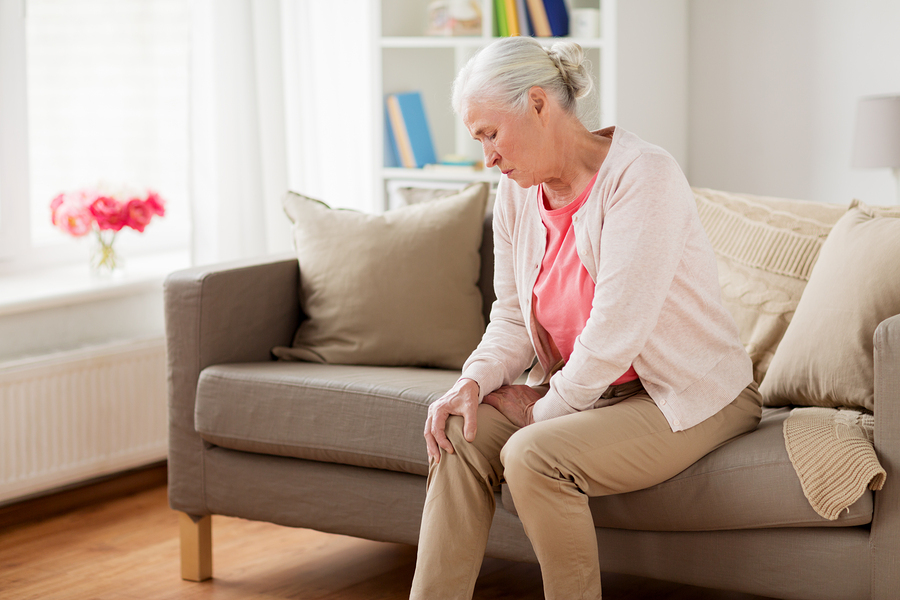 old age health problem and people concept - senior woman suffering from pain in leg at home