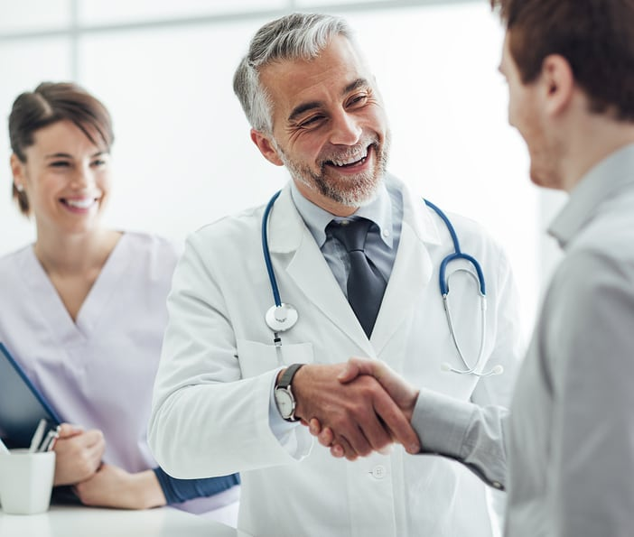 Smiling doctor at the clinic giving an handshake to his patient healthcare and professionalism concept