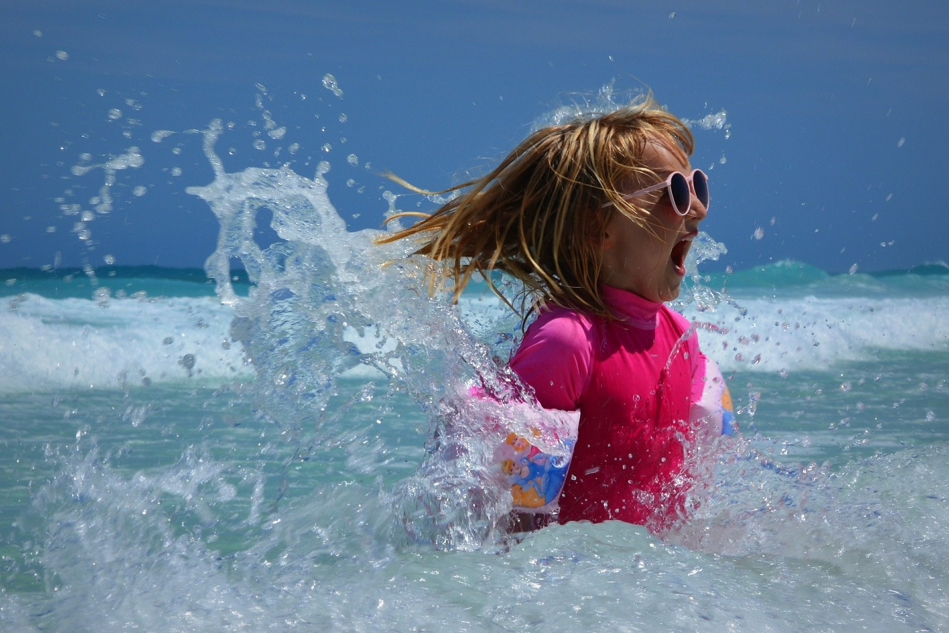 girl playing in the water with portective sunglasses and shirt