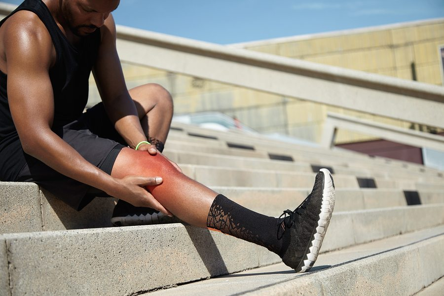 Young sportsman with strong athletic legs holding knee after suffering ligament injury during running workout sitting on stairs outdoors rubbing red sore area with painful expression on his face