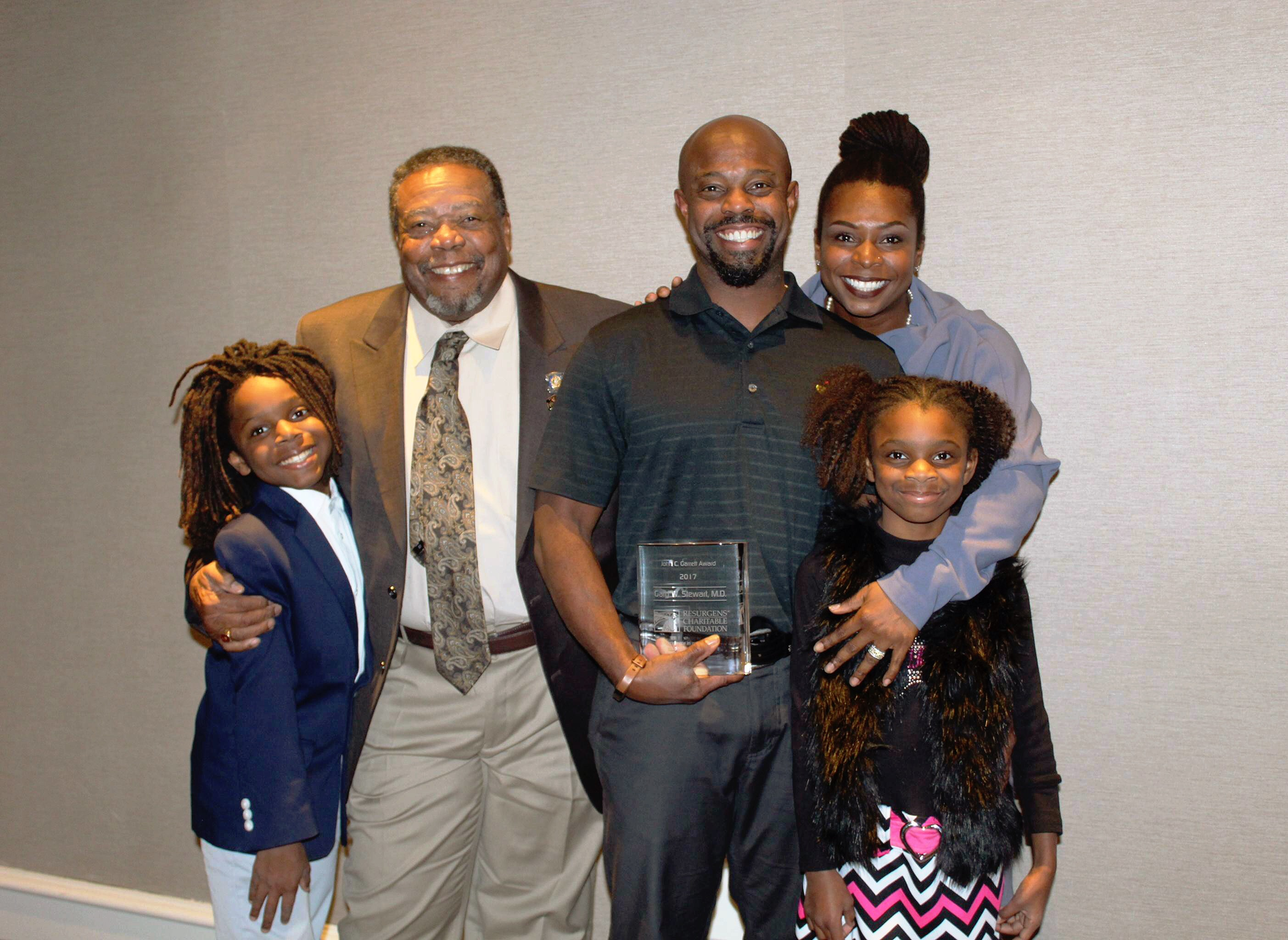 Family posing for picture with man holding award