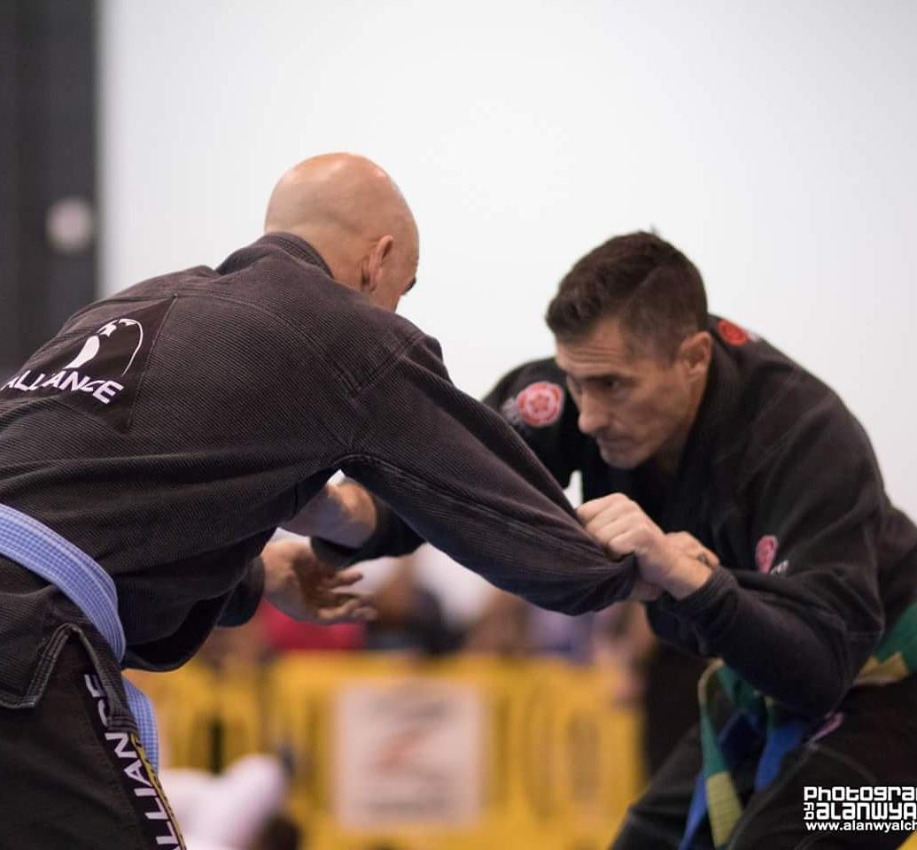 Two men sparring jiu jitsu