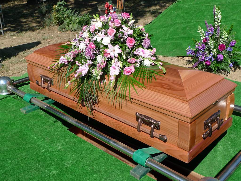 Wood casket with white and pink flowers