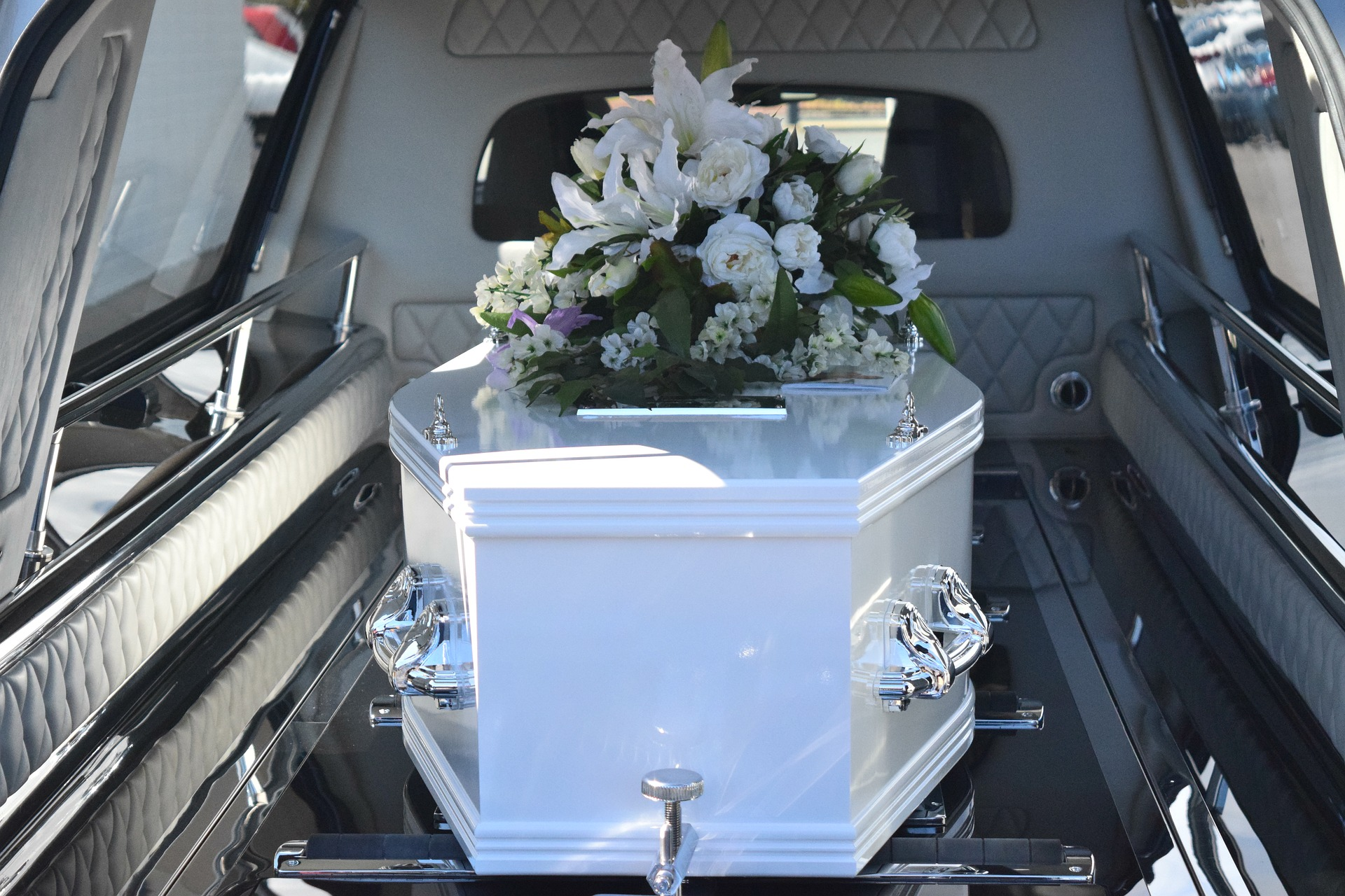 White coffin in hearse with flowers