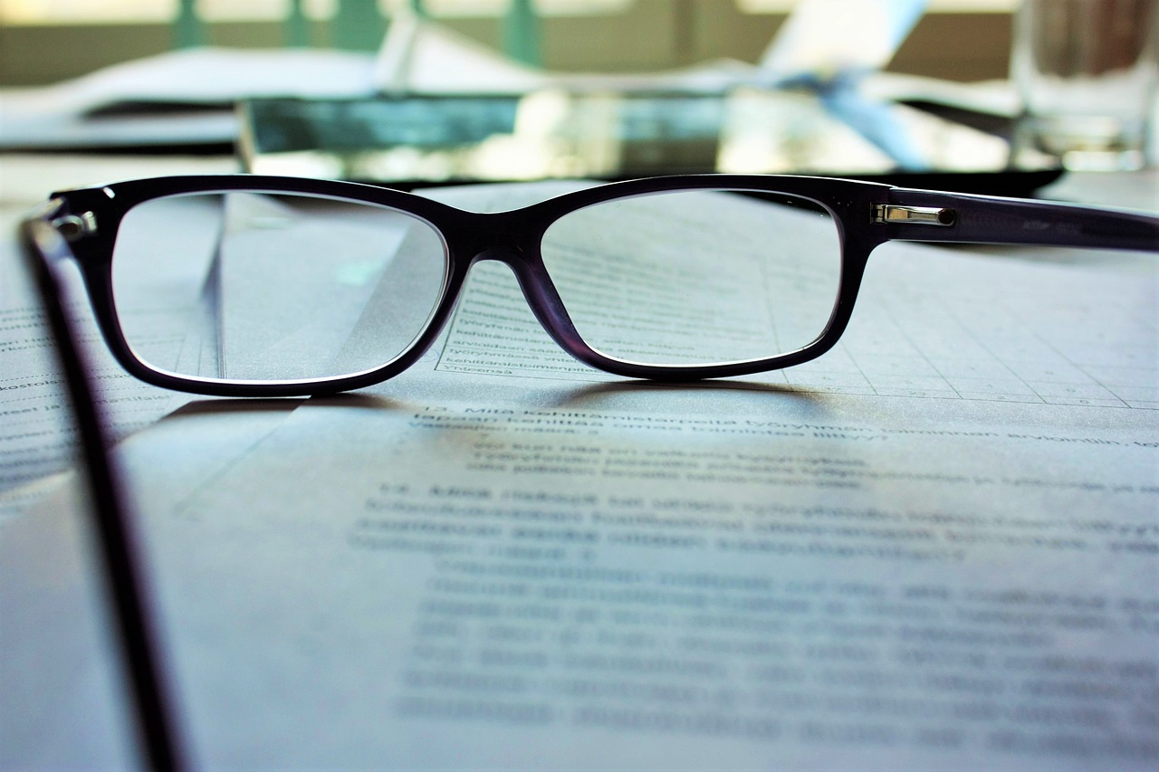 glasses sitting on top of papers