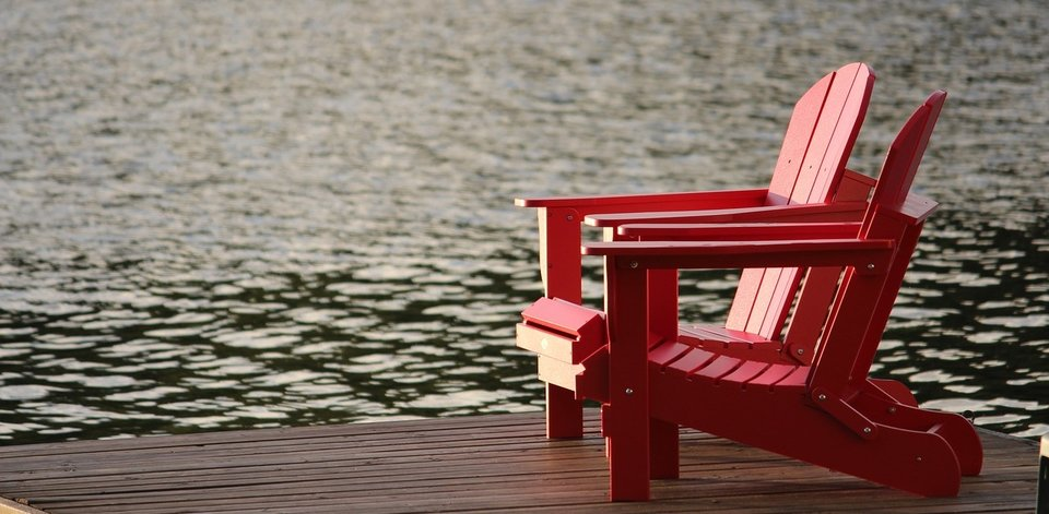Two red chairs on a dock by the ocean