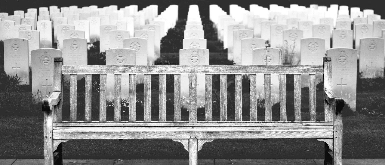 Bench in front of headstones in cemetery